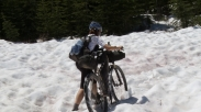 "Mary Metcalf-Collier pushes her bike in snow while racing in Tour Divide in 2008. She was the first woman to race and complete the 2,711-mile route along the Continental Divide. Photo credit: ""Ride the Divide"""
